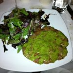 Picture of a steak with green sauce and salad