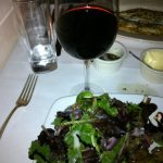 picture of edge of my plate with salad, wine, water glass, butter, oil and fork